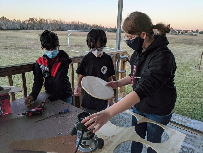 Amy Campbell (Systems Integration Co-Lead, Base Lead, CAD Specialist) demonstrates wheel routing with Jeremiah George and Albert Lee.